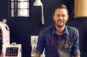 Young male hipster smiling at his place of work
