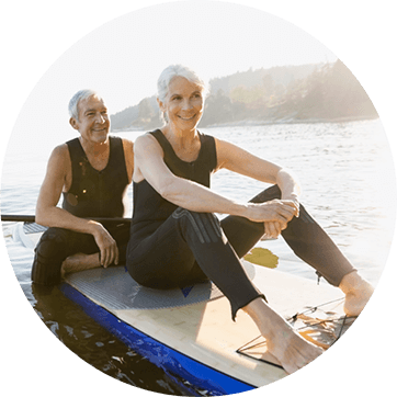 An active couple of seniors sitting on a paddleboard