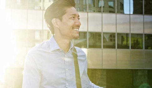 A young casually-dressed man smiles in front of an office building as the sun shines behind him.