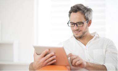 A man wearing dark-rimmed glasses smiles as he reads a digital tablet screen .in his home