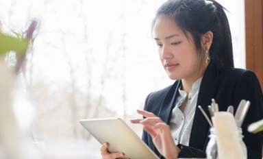 A young woman in business casual attire sits in front of a window, reviewing her investments on a digital tablet.
