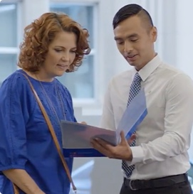 A man in a tie with a close-cropped haircut shows a folder of investment documents to a woman in a blue shirt.