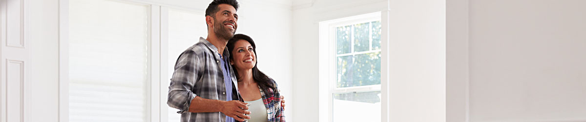 A young couple stands in their new, unfurnished kitchen smiling and embracing.