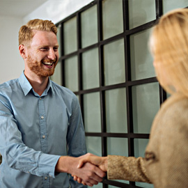 A smiling man shaking the hand of a woman after having agreed on the terms of a conditional offer.
