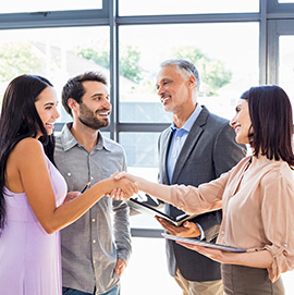Young couple shaking hands with male and female real estate experts.