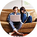 Couple figuring on couch with laptop, reading about mortgage payments