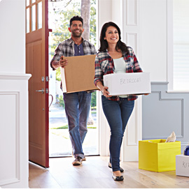 Smiling young couple carrying boxes through the front door of their new home on moving day.
