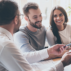 Smiling young couple reviewing home buying options with their real estate agent.