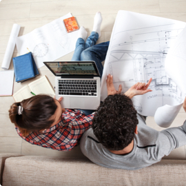 Looking down on a man and woman sitting together on a couch with a laptop and floor plans to a home.