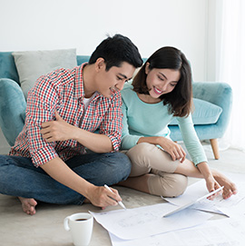 Smiling young couple sitting on the floor of their home reviewing financial paperwork.