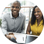 Young couple smiling and talking to a Mortgage Specialist at a bank.
