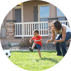 Mother playing soccer with her son in their yard.