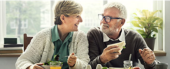 A man and woman in their sixties are eating lunch and smiling at each other. Sun streams in through a window behind them.