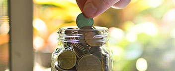A hand adding pennies to a jar