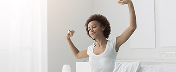 A woman wakes up on her bed and stretches her arms